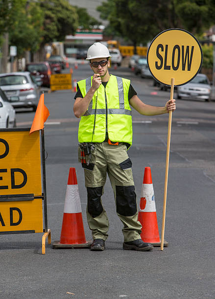 traffic controller talking to radio and holding slow sign stock photo
