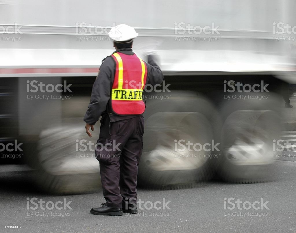 Traffic Cop With Motion-Blurred Truck stock photo