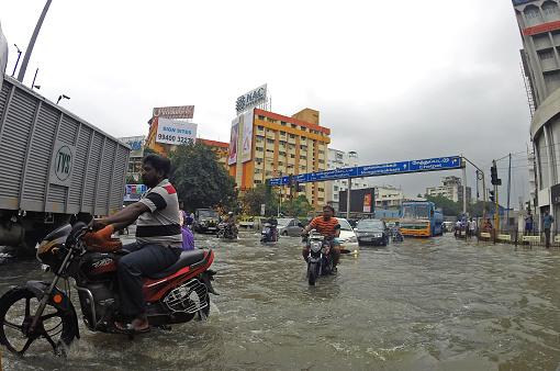 Chennai, India - 3 December 2015: Motor bikes and vehicle traffic drive through a flooded intersection in Channai, India.