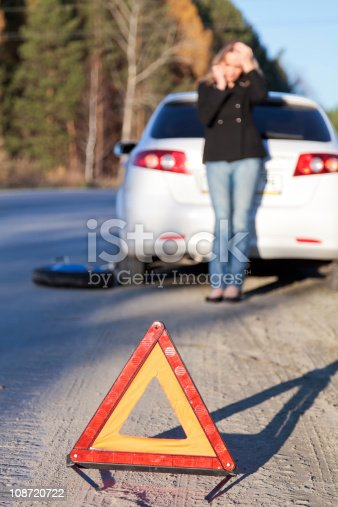 104275470istockphoto Traffic hazard triangle with young woman and white car 108720722
