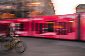 Amsterdam, Netherlands - May 03, 2016: Motion blurred picture of a woman riding bike behind of  city tram evening time in street of Amsterdam, Netherlands