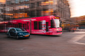 Amsterdam, Netherlands - May 03, 2016: Motion blurred picture of a car behind of city tram evening time in street of Amsterdam, Netherlands