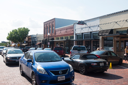 Traffic in downtown Plano with people on sidewalk