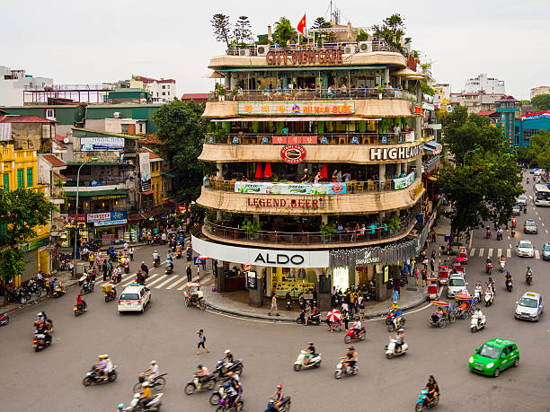 Traffic in Hanoi, Vietnam View of the traffic in Hanoi, Vietnam in front of the City View Cafe building on a gloomy afternoon. hanoi stock pictures, royalty-free photos & images