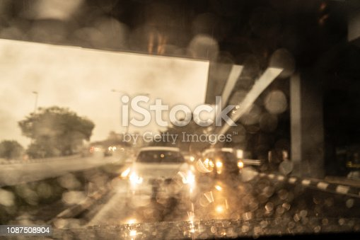 1054750504 istock photo Traffic in heavy rainy day with road view inside the car window with rain drops. 1087508904