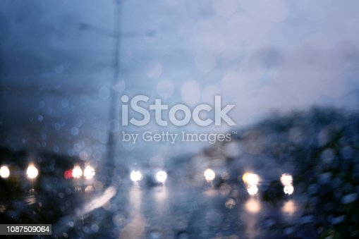 1054750504 istock photo Traffic in heavy rainy day with road view inside the car window with rain drops bokeh. 1087509064