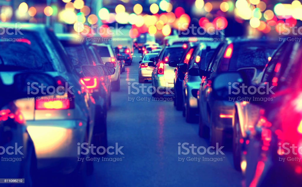 Driving a car in a a city with a traffic jam at night during the rush...