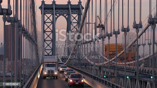 New York Usa - October 2: Vehicles caught in traffic jam driving over Manhattan bridge at beautiful misty pink dawn with downtown Manhattan business district skyscrapers in the background
