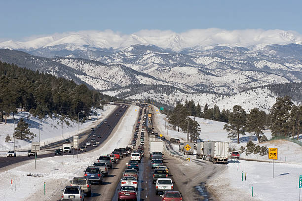Traffic jam westbound I-70 highway with snow covered mountains Colorado stock photo