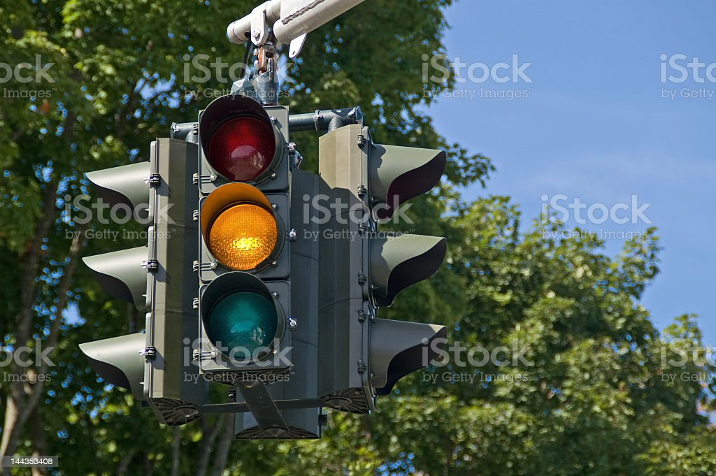 Traffic light in front of green trees with yellow light lit stock photo