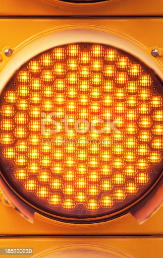 A close up of an amber led traffic light.