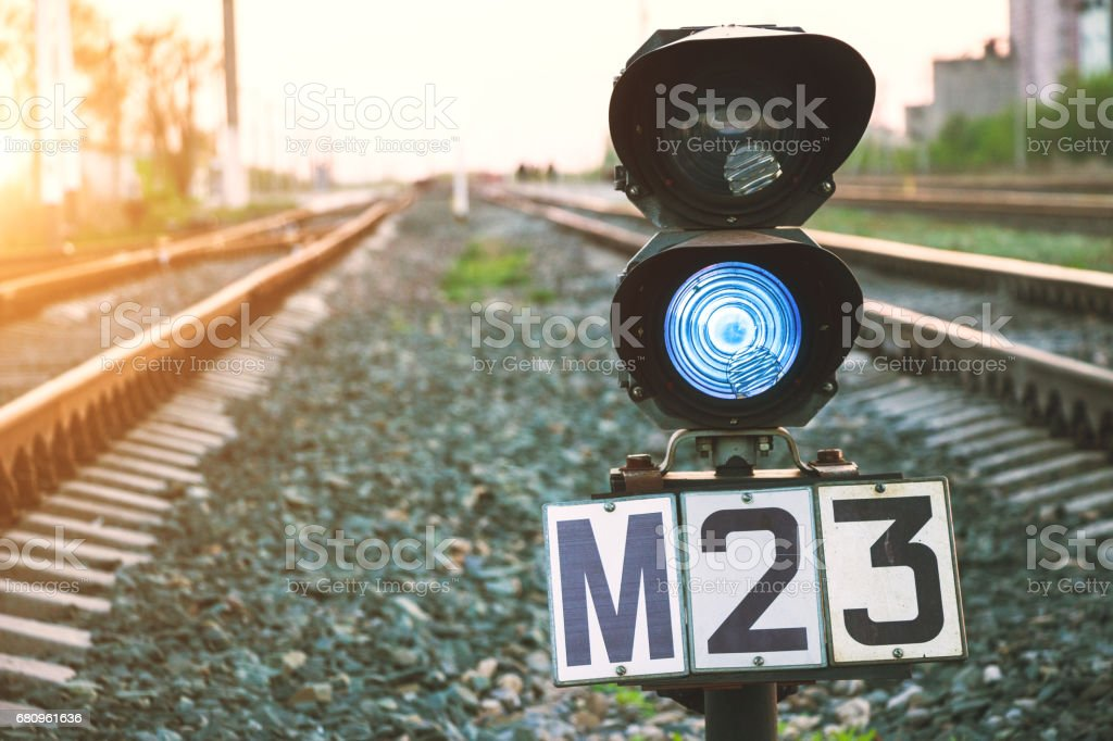 Traffic light shows blue signal on railway. Prohibiting signal. Railway station. Regulation and control of movement. Travel by train. royalty-free stock photo