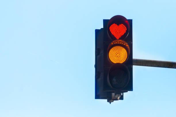Semáforo con una señal en forma de corazón rojo contra un cielo azul - foto de stock