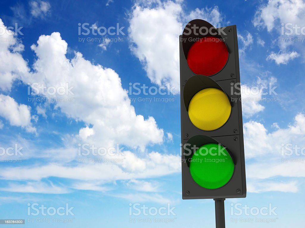 Traffic lights against the blue cloudy sky stock photo