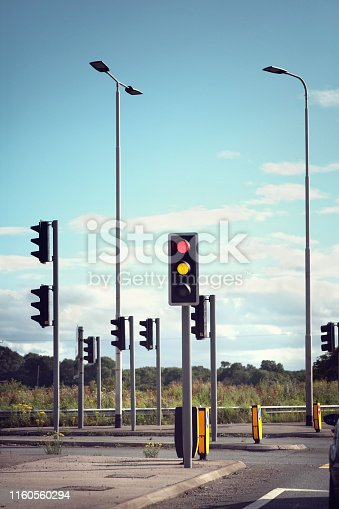 istock Traffic lights for cars on a road changing from red to green 1160560294