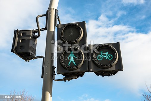 Green traffic lights for pedestrians and cyclists against blue sky with clouds. Edinburgh, Scotland, UK.