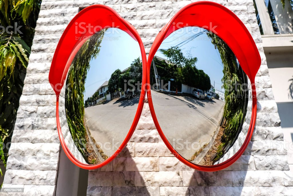 Traffic mirror on the wall at intersection or curve of road, safety and security concept, close up stock photo