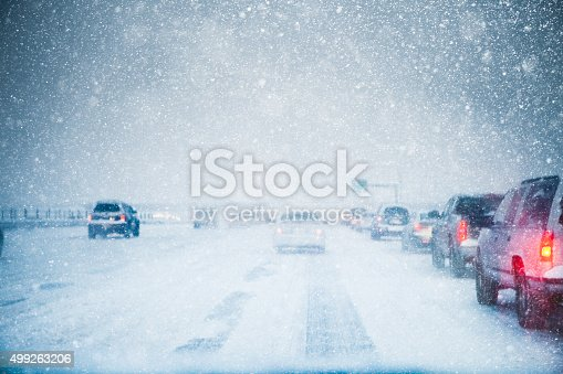 Winter weather and slow moving traffic creeping along a snow covered and icy freeway in a winter snow storm blizzard. Taillights are on in low light and low visibility road conditions. Copy space available. High resolution color photograph with horizontal composition.