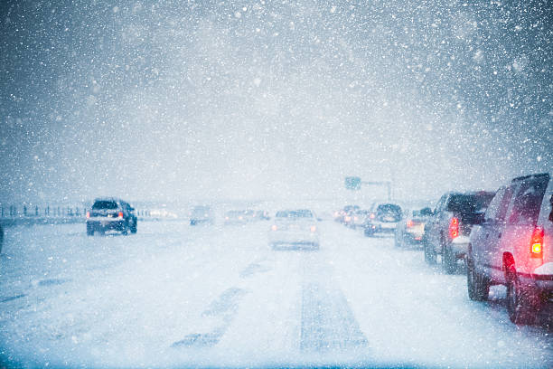 traffic moving slowly away on in a winter storm - weather stock photos and pictures