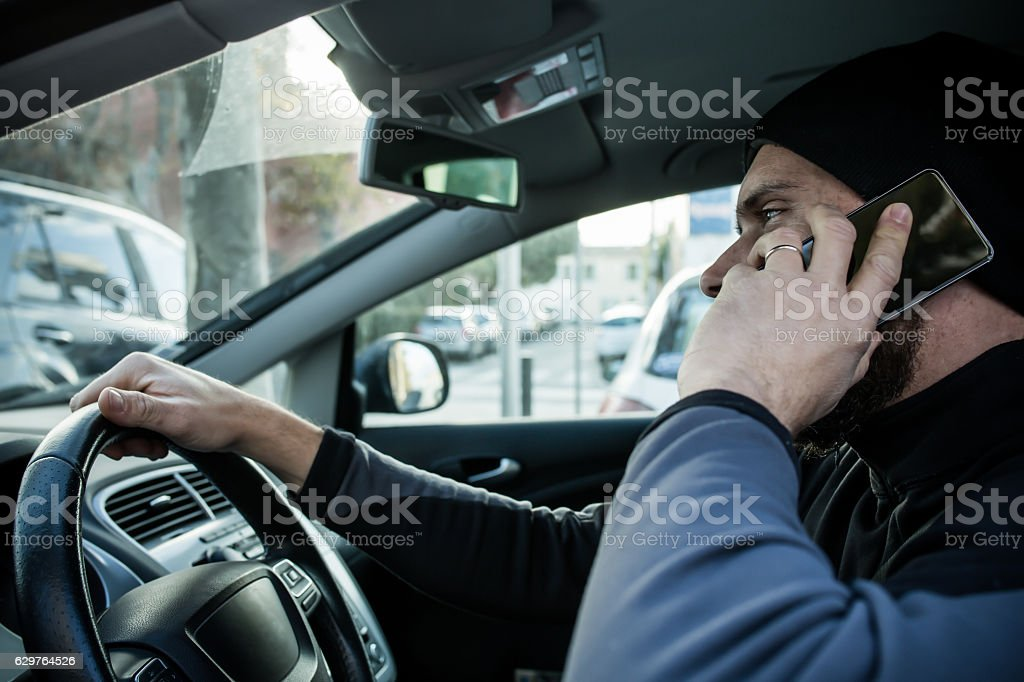 Traffic offenses man with smartphone driving stock photo