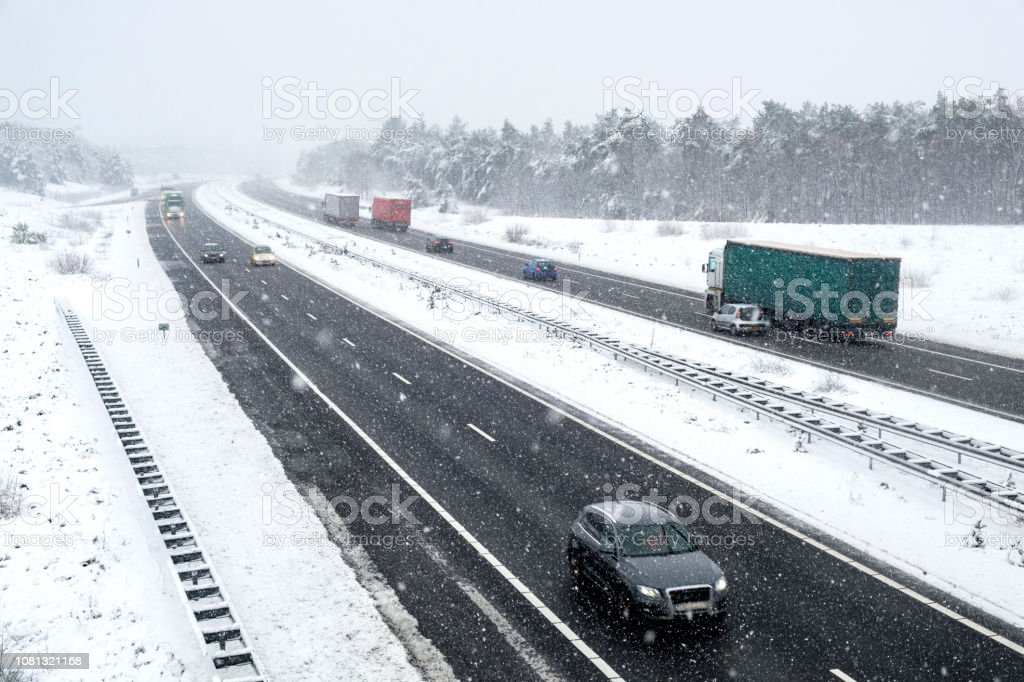 Traffic on a highway during a snow blizzard in winter stock photo
