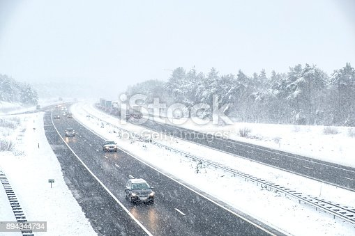 1127834626 istock photo Traffic on a highway during a snow blizzard in winter 894344734