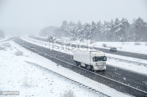 1127834626 istock photo Traffic on a highway during a snow blizzard in winter 894345158