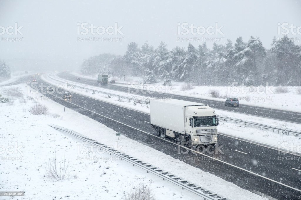 Traffic on a highway during a snow blizzard in winter - foto stock