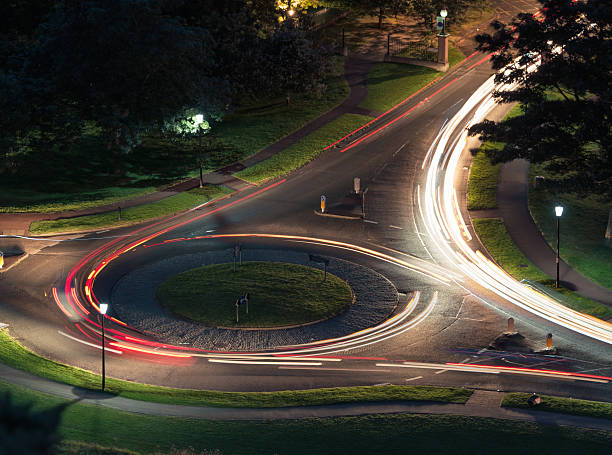 traffic on a roundabout at night - rond point carrefour photos et images de collection