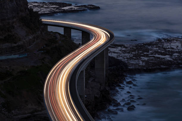 Traffic on Bridge Car light trails on Sea Cliff Bridge, a balanced cantilever bridge located south of Sydney, New South Wales, Australia speed stock pictures, royalty-free photos & images