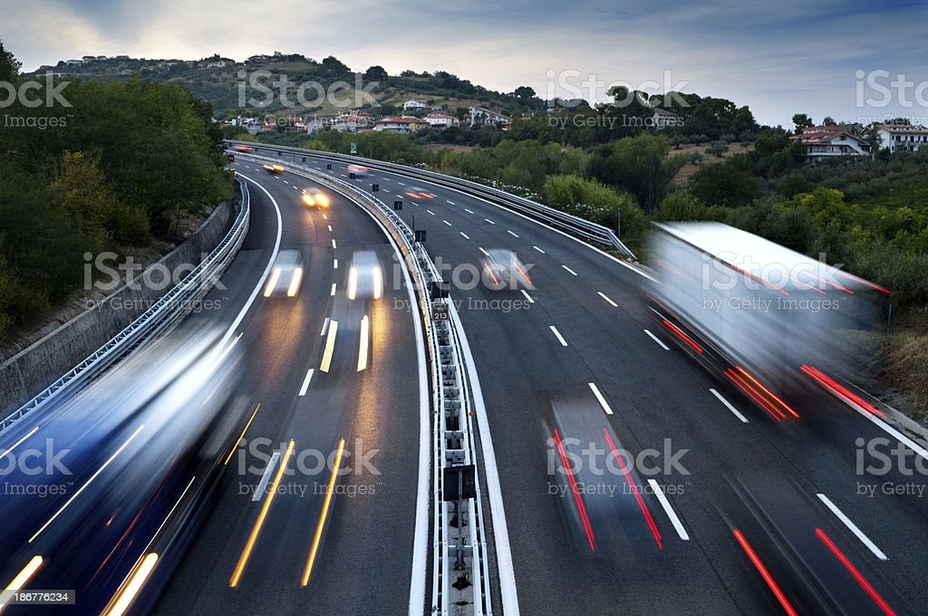 Traffic On Highway At Dusk, With Blurred Cars And Trucks stock photo