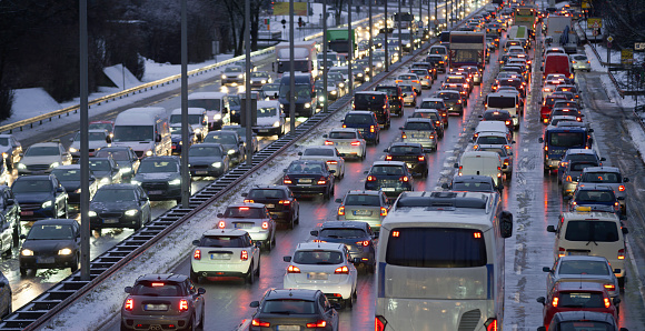 Traffic jam on highway during snow storm at dusk.