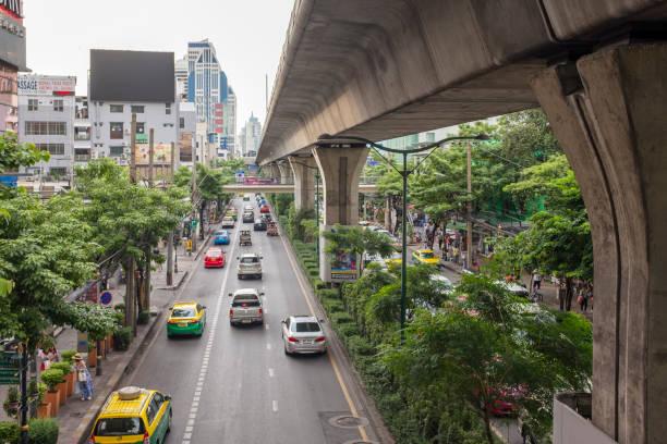 traffic on sukhumvit road in bangkok, thailand - motorbike, umbrella stock photos and pictures