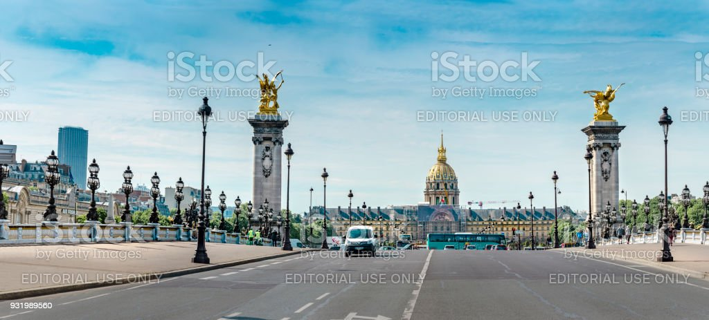 Traffic on the famous Pont Alexandre III bridge in Paris with view of Palais Bourbon, Assemblee Nationale the French Parliament and Montpernasse skyscraper at background. Panoramic view stock photo
