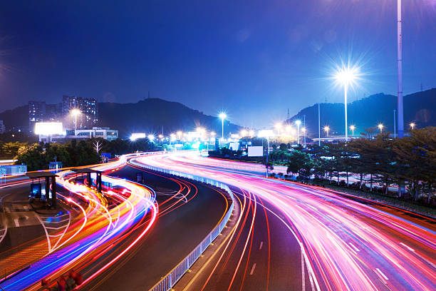 traffic on urban road and cityscape at night stock photo