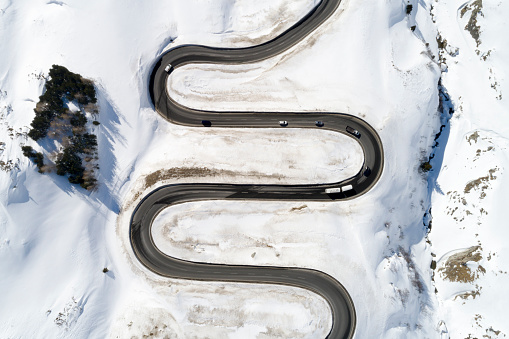 Aerial view of curvy, winding Alpine road with traffic in winter, Julier Pass, Canton of Graubunden, Switzerland.