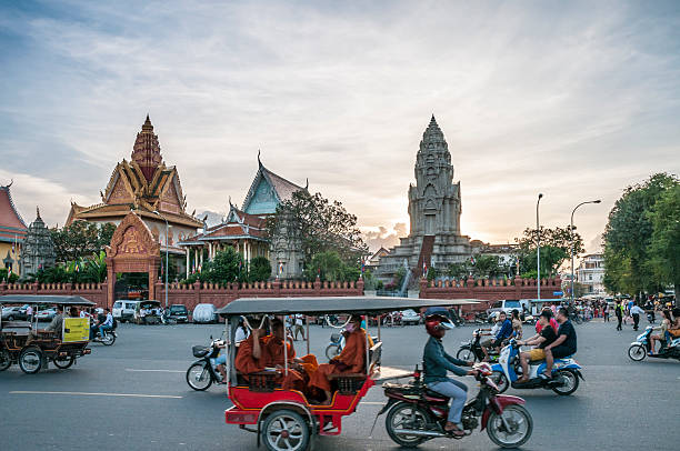 traffic outside wat ounalom at sunset in phnom penh, cambodia - motorbike, umbrella stock pictures, royalty-free photos & images