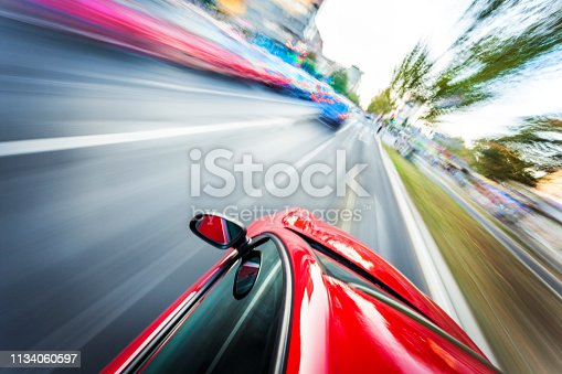 View from a fast car in motion on the highway or boulevard with motion blur and focus on the car hood.