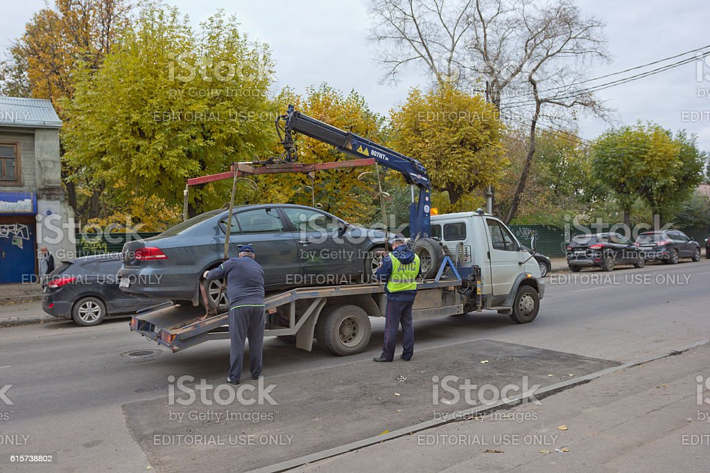 Traffic police officer lifting car on tow truck in Ryazan stock photo