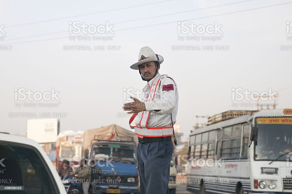 Traffic police officer waving at cars in Haryana, India stock photo