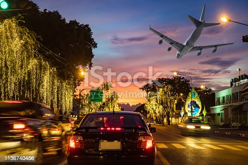 istock Traffic road in capital with light car and airplane flying in route beautiful festival 1136740456