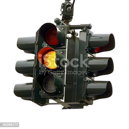 Traffic signal, hanging with white background amber light illuminated.