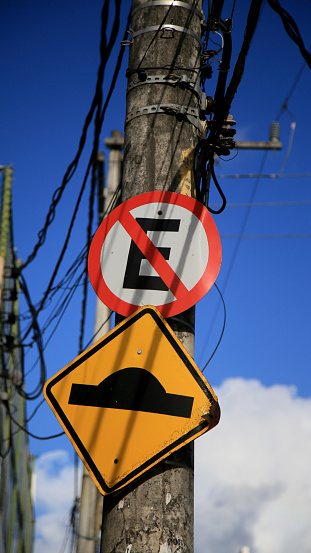 salvador, bahia / brazil - july 4, 2020: traffic signs indicate speed bumps and forbidden to park on a pole attached to the electricity grid in the Cabula neighborhood in the city of Salvador.