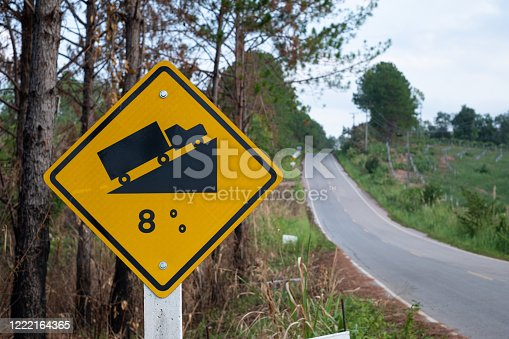 Traffic signs warning up to hill steep road sign to slope a steep climb 8 percent gradient in the road ahead at green grass in the background