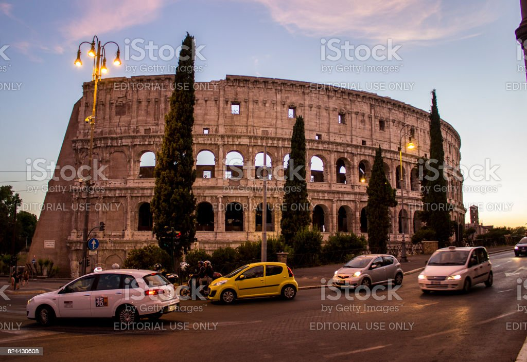 Traffic stream in front of Coliseum during sunset in Rome, Italy stock photo