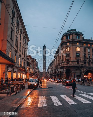 Traffic of vehicles and people walking along The Via Francesco Rizzoli is main street of Bologna city and two towers (Torre degli Asinelli) on background at night in Bologna, Italy