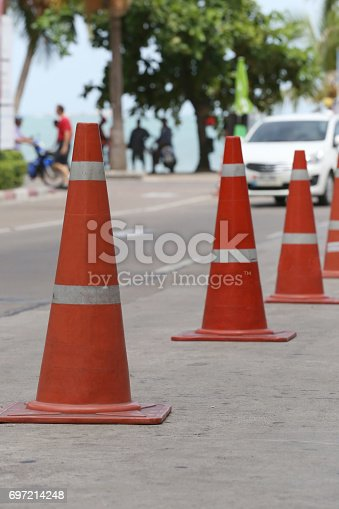 istock Traffic warning cone in row to separate route in walkway for pedestrians. 697214248