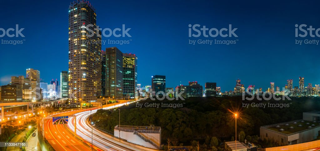 Rush hour traffic zooming along elevated highways overlooked by the...