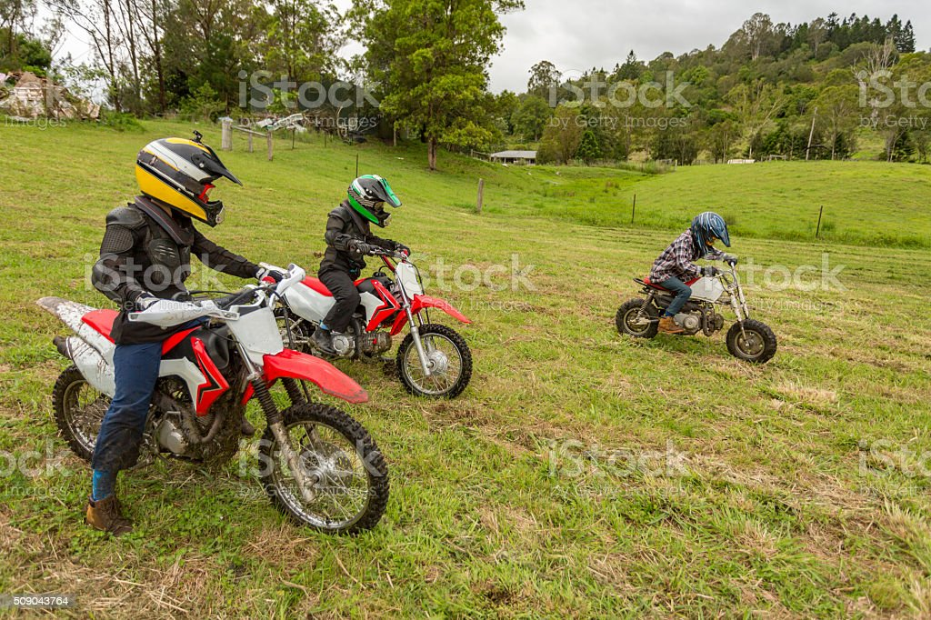 Trail Bike Riders in a Paddock on a Farm stock photo