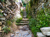 Old stairway and narrow rock walls heading up to a mountain trail between towns in Manarola Italy